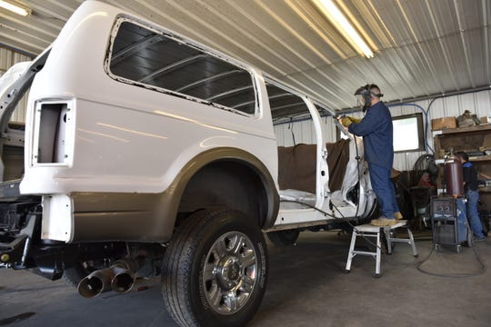 Alex Sanchez grinds a weld on a custom built Ford Excursion at Custom Autos By Tim in Guthrie, Oklahoma.