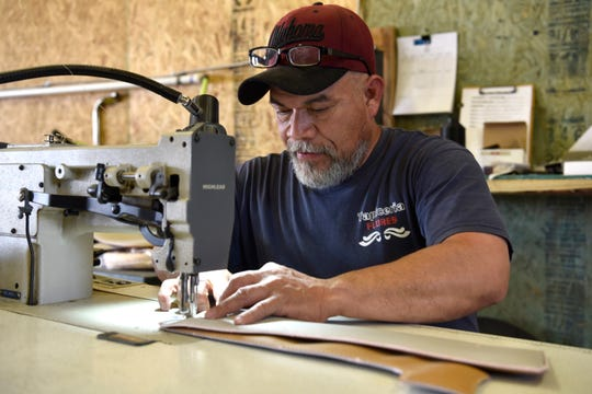 Polo Geronimo sews together upholstery pieces for a Ford Excursion at  Custom Autos By Tim in Guthrie, Oklahoma.