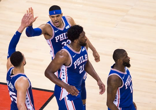 Philadelphia forward Tobias Harris, a former Piston, high-fives guard Ben Simmons as teammates Joel Embiid (21) and James Ennis III (11) look on after the win over Toronto.