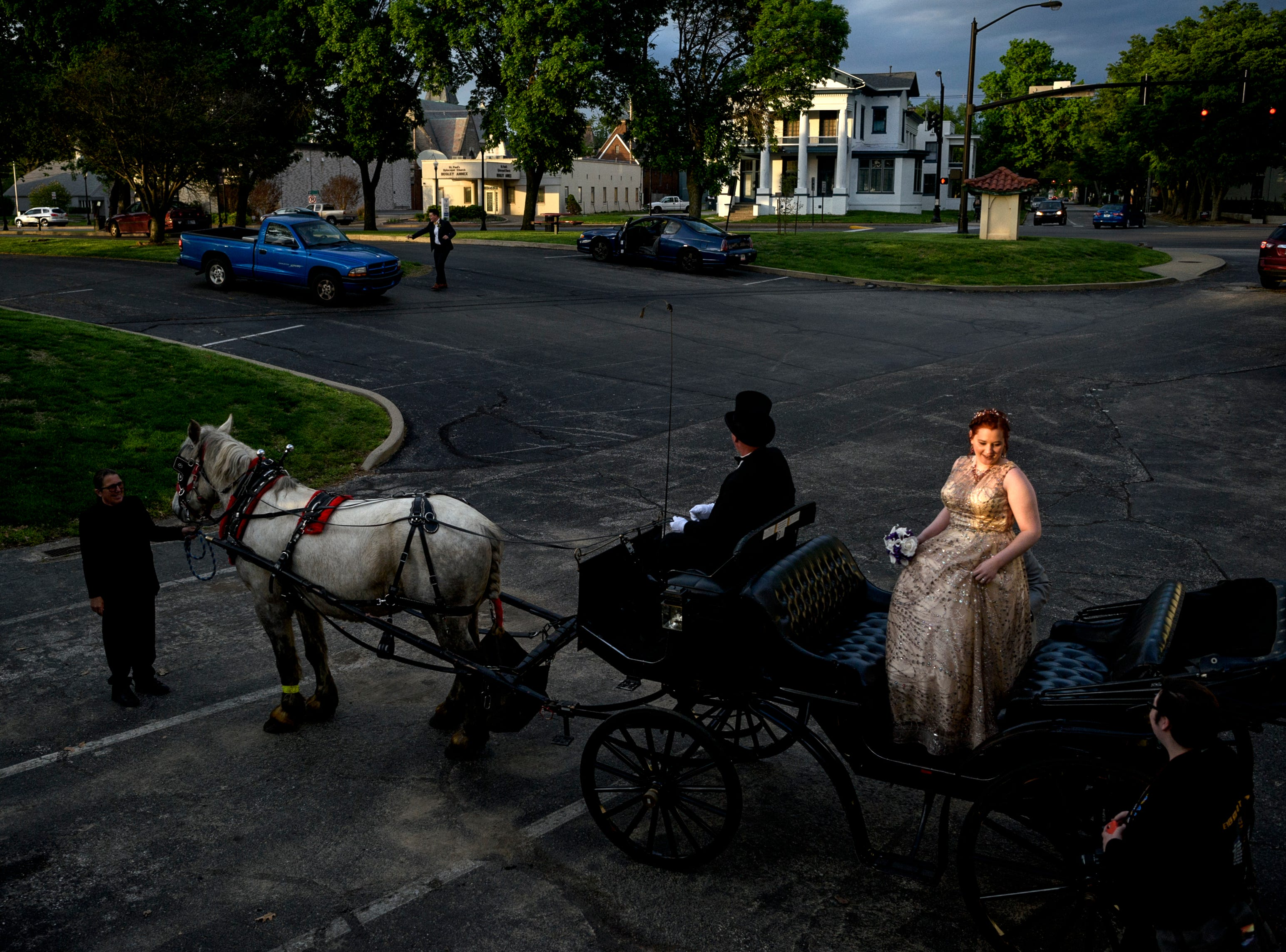 Castle High School student Rachel Landrum, center right, gets back on a Horseshoe Bend Carriage Co. carriage after making a pit stop to take prom pictures by the river with her boyfriend Conner Gorman, not pictured, and CHS student photographer Randy Cox, bottom right, in downtown Evansville, Ind., Saturday, April 27, 2019. Randy, center left, and Sheila O'Risky, far left, lead the couple and photographer through downtown Evansville before taking them to their prom at Old National Events Plaza.