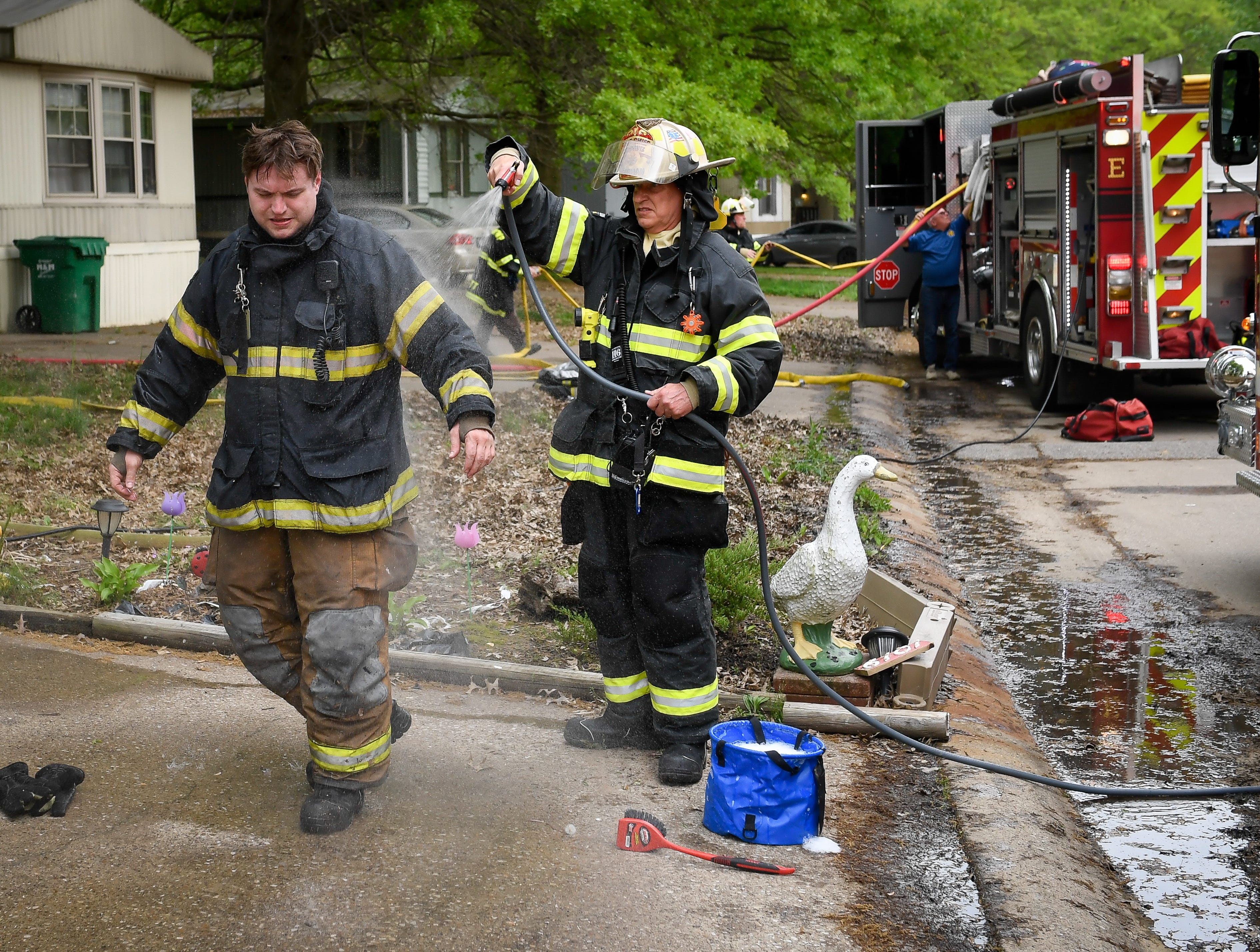 Assistant Chief Rick Schnautz, with the German Township Fire Department, helps decontaminate James Hines with the McCutchanville Fire Department after fighting a dryer fire at 6101 Danville Drive in Evansville Tuesday, April 30,2019.