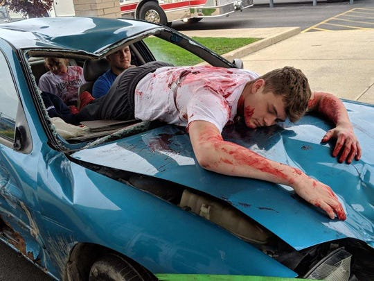 Clyde junior Jack Morrison lies on the hood of a car to reenact the death of a student who went through the windshield in a drunken driving crash.