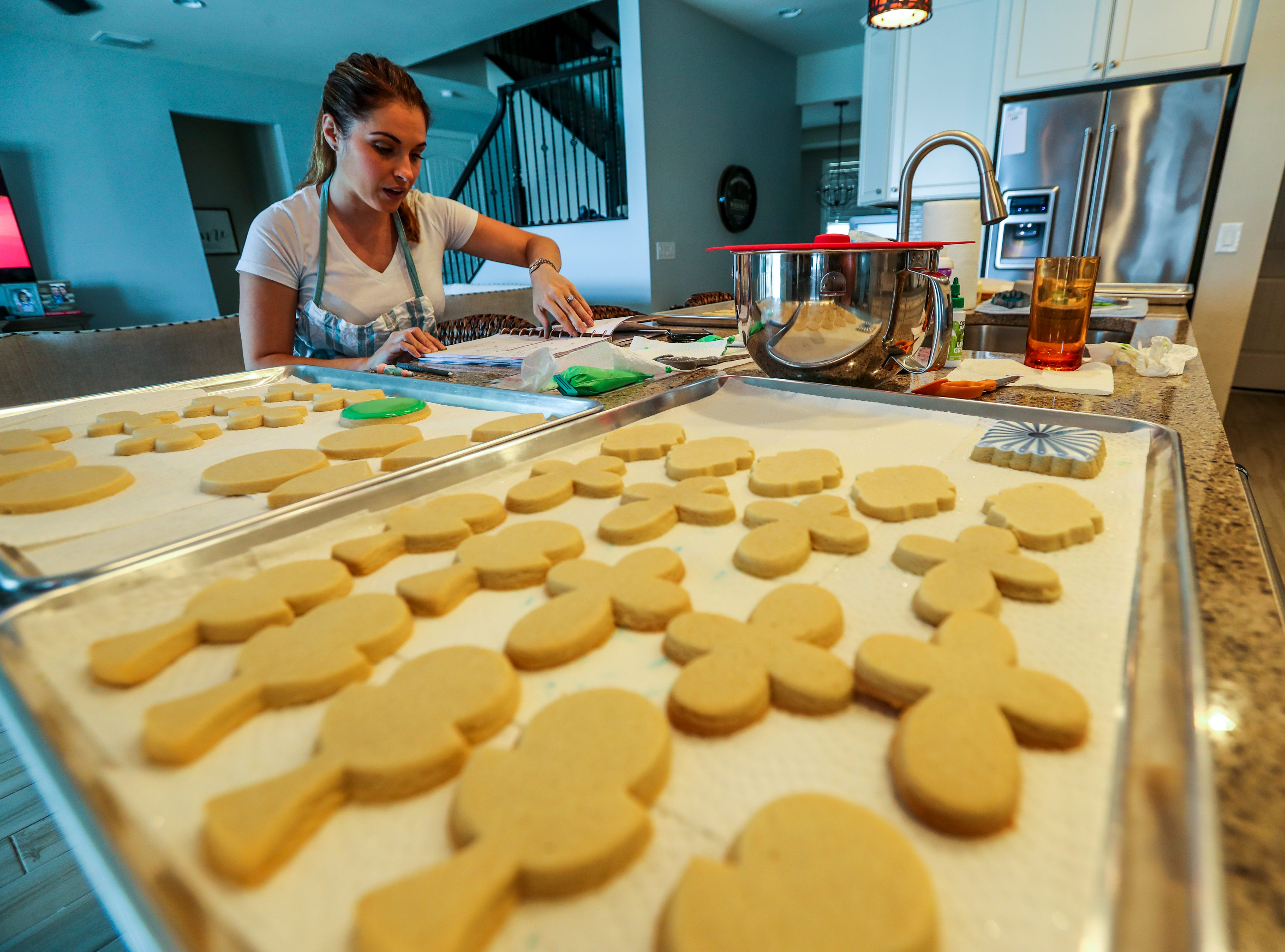 """Amanda Arrington operates """"A Little Cookie Shoppe"""" from her home near the village of Estero. She bakes and decorates unique, custom cookies for different occasions. She's also a mom with six kids.  Amanda looks to her calendar as she talks about all the orders she has to make this week. April 30, 2019."""