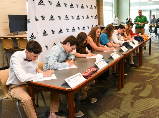 Easley High School athletes sign letters of intent during a signing day ceremony at Easley High School Tuesday. From left; Parker Cassell (Erskine College baseball, Devyn Bond (Southern Wesleyan University baseball), Aubrey Lewis (Southern Wesleyan University softball), Tarrah Semones (Erskine College track), Calista Turner (Southern Westlyan University soccer), Gabe Golden (Erskine College soccer), Grace Rookard (Limestone College competitive cheer), Kylie McKean (Erskine College beach volleyball), and Ethan Boyles (Newberry College football).