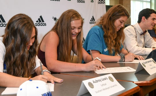 Easley High School athletes, from left; Aubrey Lewis (Southern Wesleyan University softball), Tarrah Semones (Erskine College track), Calista Turner (Southern Westlyan University soccer), and Gabe Golden (Erskine College soccer), sign letters of intent during a signing day ceremony at Easley High School Tuesday.