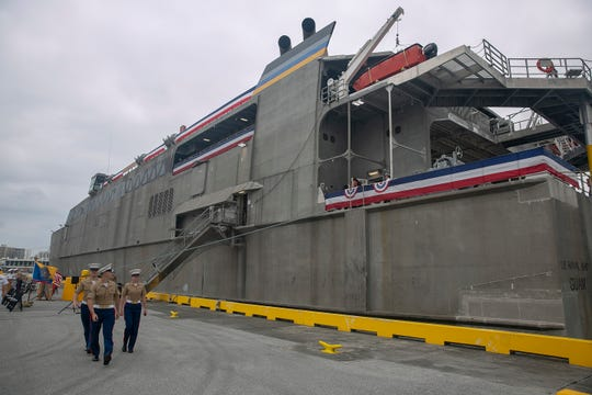 NAHA, Japan—Marines walk past Military Sealift Command's high-speed transport USNS Guam after the christening ceremony of USNS Guam, April 27. The ship is an aluminum catamaran designed to be fast, flexible and maneuverable, even in austere port conditions, making the vessel ideal for transporting troops and equipment quickly.