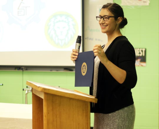Emily Salinas, a ESL teacher and a coordinator of the exchange program, presenting an award of completion to a student participating in the program