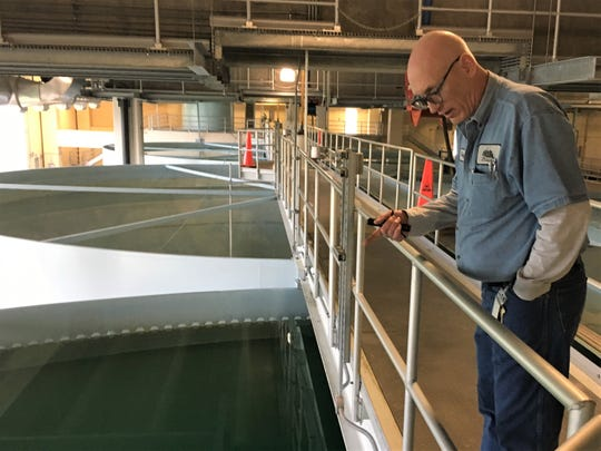 Craig Meacham, the senior water treatment plant operator for Iowa City, describes how the spinning water clarifier allows for heavier sediment to fall out of suspension and collect at the bottom of the conic basin.