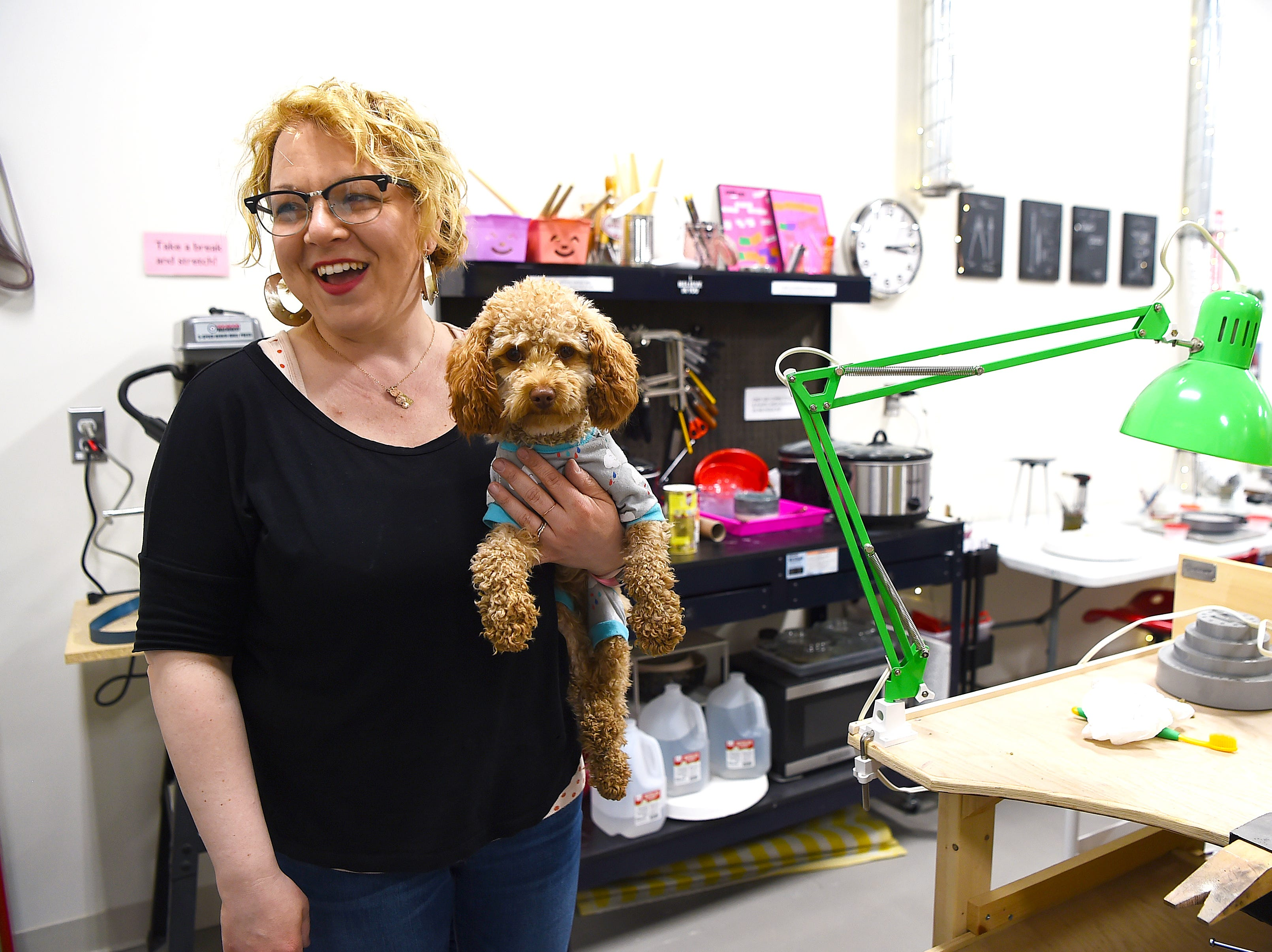 Elaan Greenfield and her dog in The Metal Smithery, her metal arts school in the South Hill Business Campus on Danby Road. Once an industrial space, Artist Alley at South Hill now houses a variety of working artist studios, with more being built to meet the demands of area artists.