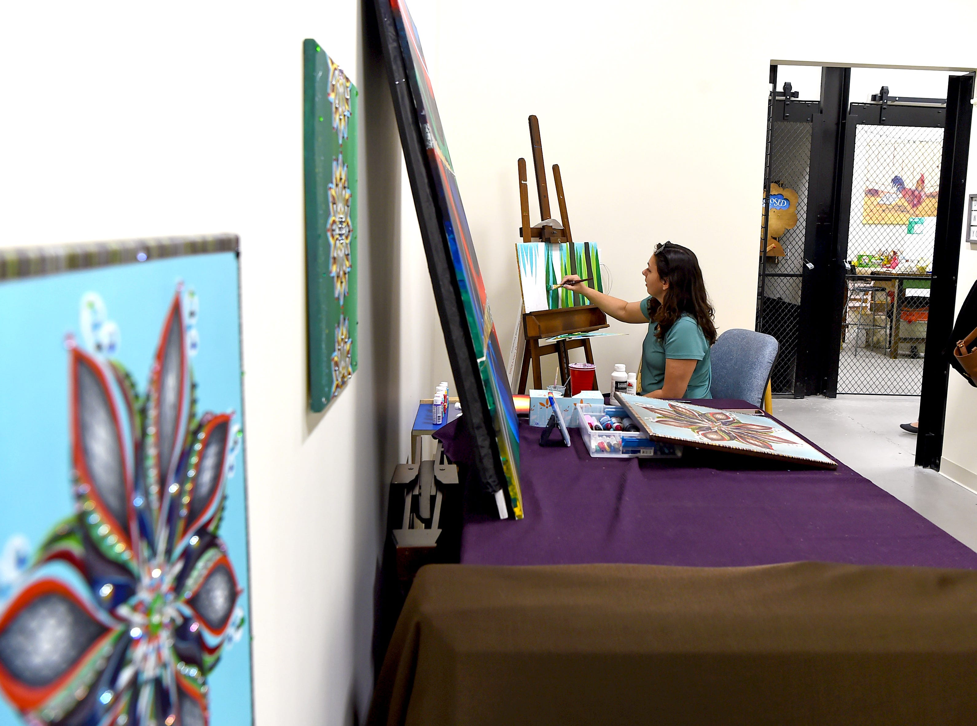 Jennifer Whitaker at work on a painting in Artist Alley studio. Once an industrial space, Artist's Alley at South Hill now houses a variety of art studios, with more being built to meet the demands of area artists.