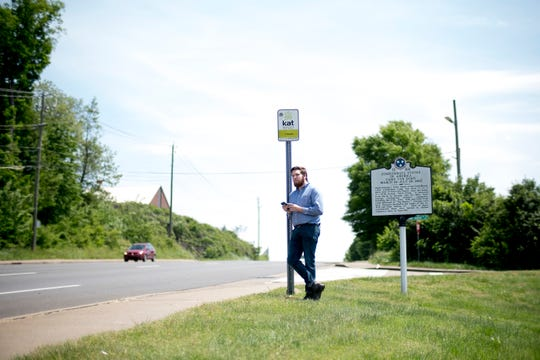 Knox News urban life writer Ryan Wilusz checks his phone for the arrival time of a bus while waiting at a bus stop on Western Ave. in Knoxville, Tennessee on Tuesday, April 30, 2019.