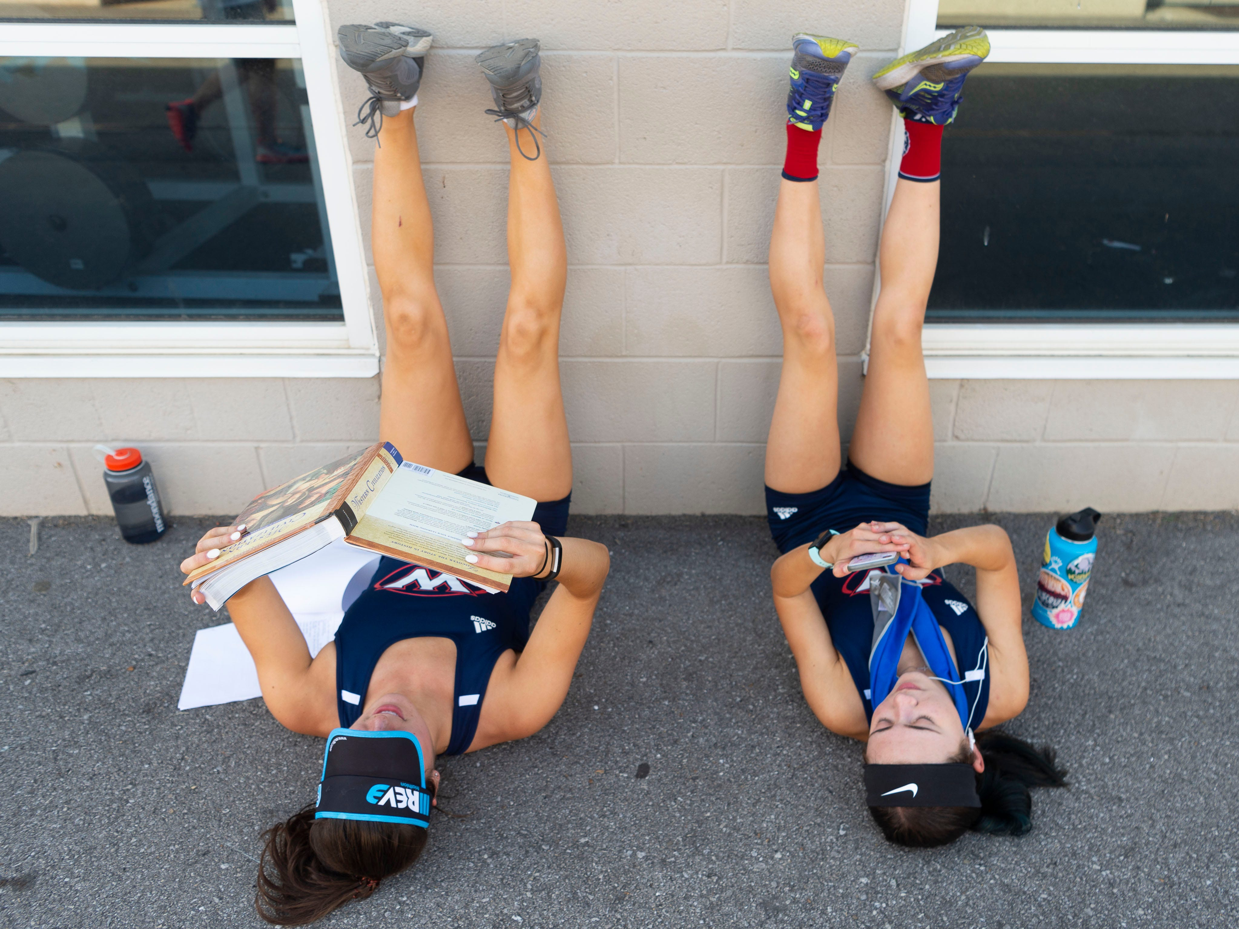 West runners Janie Holecek studies for her AP European history class as she and  teammate Hannah Burkhart rest their legs after helping win the 4x800 meter relay at the KIL Championships at Hardin Valley Academy on Tuesday, April 30, 2019.