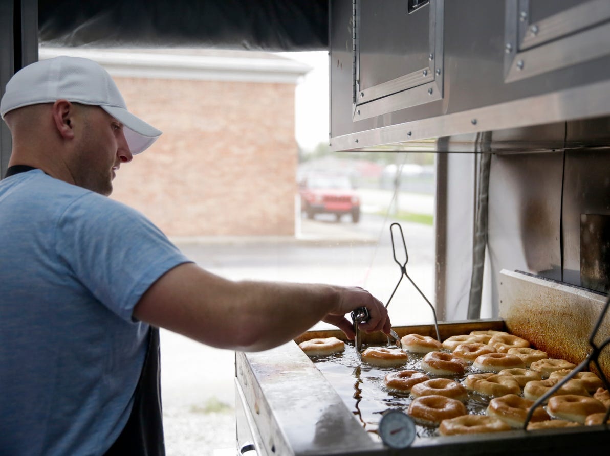 Nate Kaelin fries up an order of donuts in the Fat Bottom Donuts food truck, Monday, April 29, 2019 in Crawfordsville.