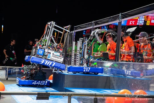 """Brighton High School robotics team """"The Technodogs"""" (far right) completing a suction double climb with their alliance partners """"The ThunderChickens"""" from Sterling Heights. The third alliance partner was a Dutch team called """"The Rembrandts."""""""