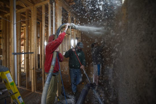 Workers blow insulation in a new build in this subdivision near Willowbrook and Forestview Drive in Haslett.