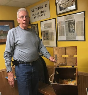 Dick Baker loves studying and compiling history, especially sports, military and genealogy. Here in his man cave he's got a ticket box, complete with ticket stubs, from the old Pete Henry Gym at Mansfield Senior propped on a bench from the gym.