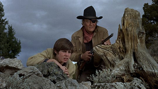 "John Wayne (right, with Kim Darby) locks and loads in 1969's ""True Grit."""