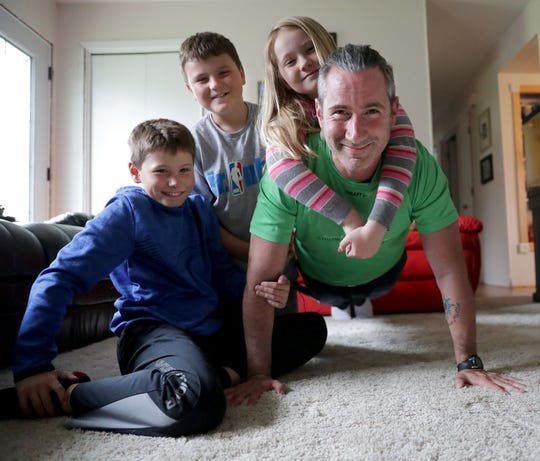 Nate Carroll with his children, (left to right) Louie, 10, Charlie, 12, and Millie, 8, in their home in Winneconne on April 29. Carroll started the Thank Law Enforcement Challenge this year. The challenge consists of thanking at least one police officer in all 50 states and 3,142 counties in America. To promote the challenge, Nate is attempting to do 1 million pushups in 2019.