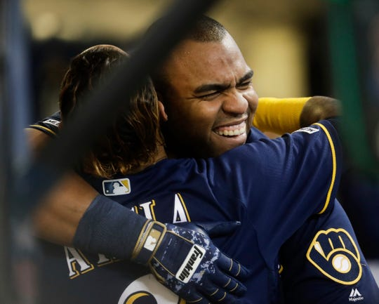 Jesus Aguilar gets a big hug from Orlando Arcia in the Brewers dugout after his three-run blast in the first inning against the Rockies on Monday.