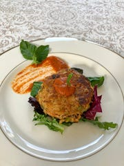 Roasted red pepper sauce dresses up this crab cake in two ways: a dollop on top and a brush stroke on the plate.