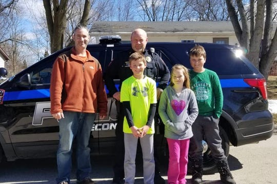Nate Carroll, left, with Winneconne Police Chief Paul Olson and Carroll's children, from left, Louie, 10, Millie, 8, and Charlie, 12, near their home in Winneconne in March.