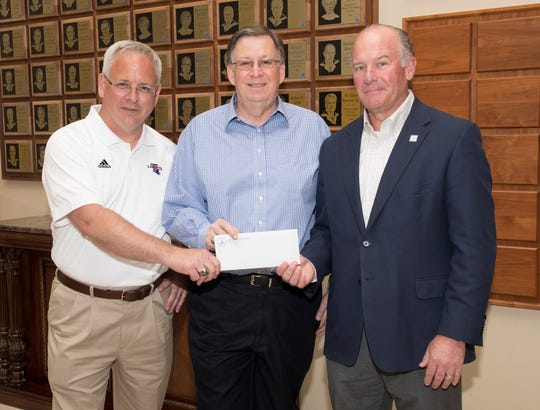 University of Louisiana System President and CEO Jim Henderson (left) and Louisiana Tech President Les Guice accept funds from Louisiana Tech University Foundation Board President Bill Hogan (right). Donations toward the University Excellence Fund are being used to assist faculty and staff members who suffered catastrophic losses during the April 25 tornado.