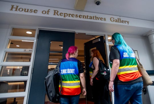 Clinic escorts Mia Raven, from left, Margeaux Hartline and Kari Crowe walk into the gallery to watch debate on the abortion ban bill at the Alabama Statehouse in Montgomery, Ala., on Tuesday April 30, 2019.