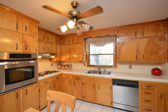The kitchen has stainless appliances, a cooktop and a built-in oven.