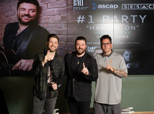 """Corey Crowder, Chris Young and Josh Hoge celebrate Young's No. 1 hit """"Hangin' On"""" during a party at BMI. The men co-wrote the song together."""