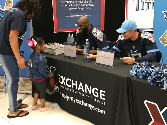 Titans players Rashaan Evans and Adam Humphries sign autographs as part of the Titans Caravan on Monday in Fort Campbell, Ky.