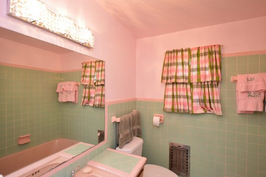 The bath features the original pink and green tile.