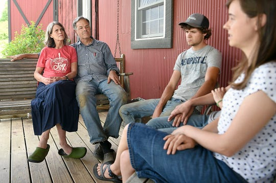 """Farmers Pam and John Dysinger sit on their porch with their son, Joshua, and daughter, Kirsten, at their Bountiful Blessings Farm Williamsport, Tenn. on Monday, April 29, 2019. John Dysinger was tapped to serve as spiritual adviser for death row inmate Donnie Johnson in 2006 and then visited him for years with his wife and kids, who grew up knowing """"Uncle Don."""""""