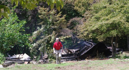 An investigator walks away from the charred foundation of Matt and Mendy Neal's Loggins Road home hours after the July 11, 2012 fire.