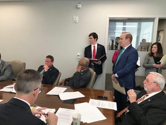 Former legislative staffer turned-lobbyist Drew Lonergan, center, stands next to Rep. Martin Daniel as he presents a bill during a legislative pre-meeting on March 5, 2019.