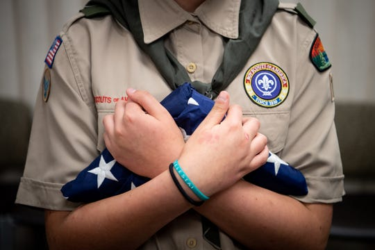Hope Bakken, 13, folds a flag during a Scouts BSA meeting at Christ Community Church in Franklin on April 29, 2019.