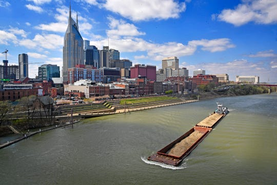 A barge cuts through the waters of the Cumberland River as it passes the Nashville skyline Sunday, March 31, 2019, in Nashville, Tenn.