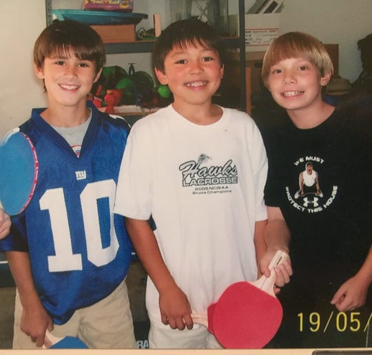 NY Giants draft pick Daniel Jones (left), with friends, sporting an Eli Manning jersey at the age of 10.