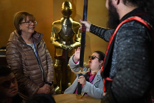 Students from St. Joseph's School for the Blind in Jersey City visit Medieval Times in Lyndhurst on Tuesday, April 30, 2019. (center) Student Daniela Duarte holds a sword with help from (right) Medieval Times knight Kyle Watkins. (left) Mary Giambona, a teacher at St. Joseph's School for the Blind, looks on.