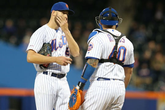 New York Mets starting pitcher Zack Wheeler (45) reacts as he talks to catcher Wilson Ramos (40) during the second inning against the Cincinnati Reds at Citi Field.