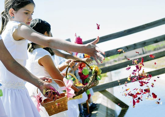 In this file photo, Las Cruces Catholic Schools student McKree Riley tosses flower petals with others at a recent Blessing of the Fields ceremony at New Mexico Farm & Ranch Heritage Museum.