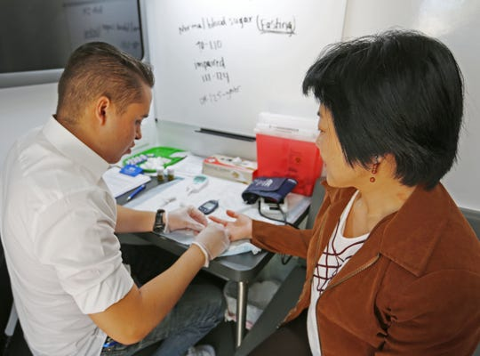 Reuben Marquez, left, assistant executive director of Southern New Mexico Diabetes Outreach, tests Chong-Hwey Fee's blood sugar level on Tuesday, April 30, 2019, at New Mexico State University, during an outreach day on campus.