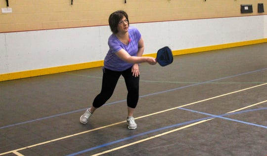Kathy Dabkowski strikes the ball during a pickleball clinic April 30 at the recreation center in Livonia.