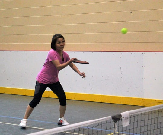 Ineko Yamakawa of Redford strikes a ball at the recreation center in Livonia during a pickleball clinic April 30.
