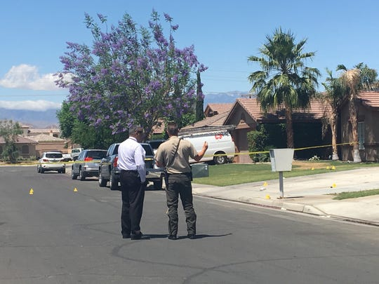 Indio police investigator place markers outside a home where authorities said a resident threatening his family was injured on Tuesday, April 30, 2019.