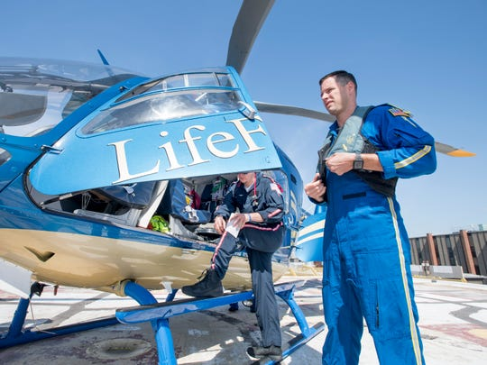 Flight nurse Colten Lander, left, and flight paramedic Tyler Bennett prepare to leave April 30 in LifeFlight's new EC135 twin-engine helicopter for a mission at Baptist Hospital in Pensacola.
