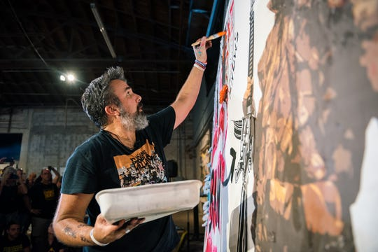 Manuel Oliver paints a mural portraying his son Joaquin, a victim of the Feb. 14, 2018, mass shooting at Marjory Stoneman Douglas High School, as a mounted trophy and U.S. Rep. Matt Gaetz, a vocal advocate of the 2nd Amendment, as a hunter.