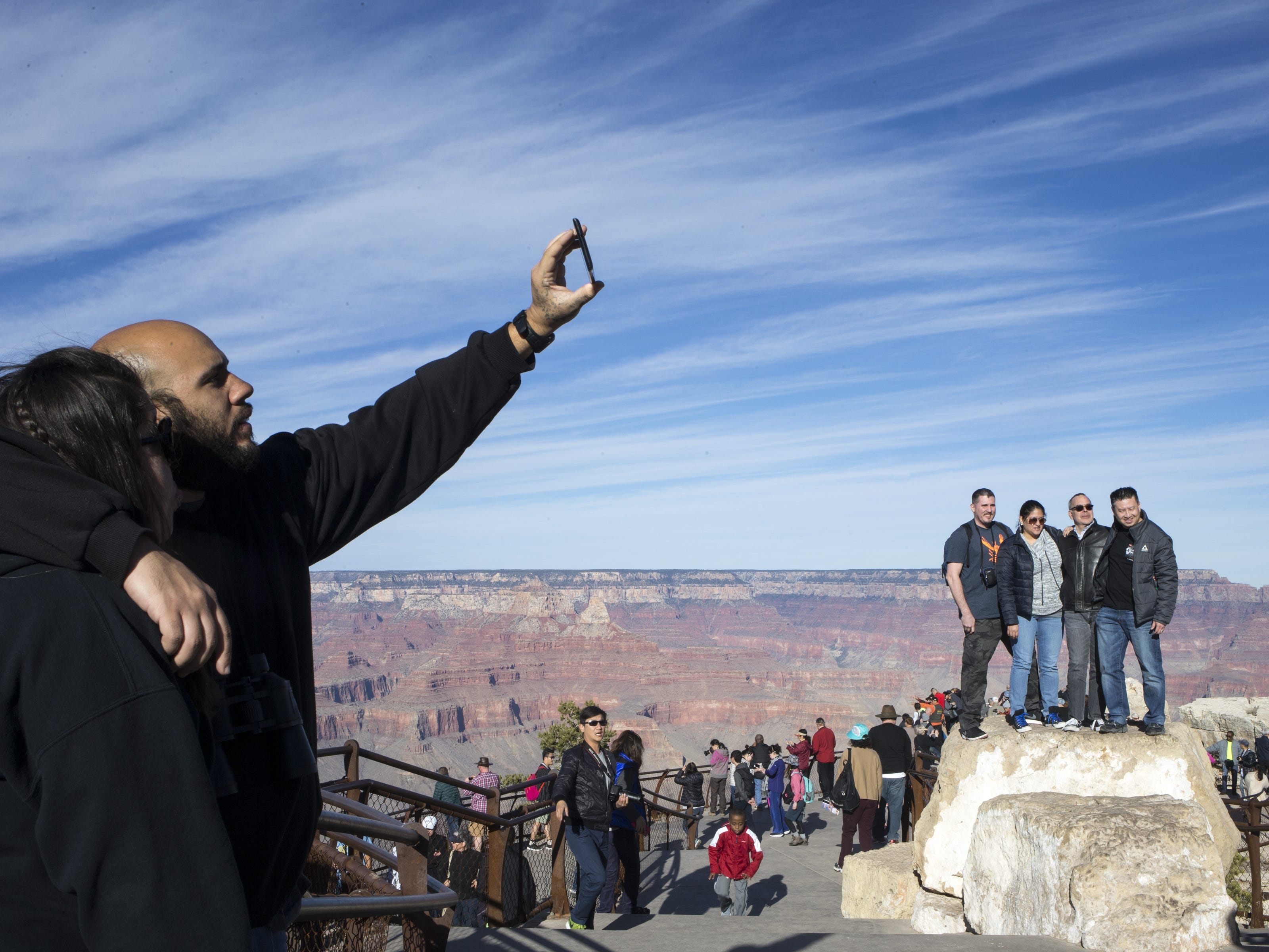 Visitors take photos from Mather Point, at Grand Canyon National Park. Railings mark the edges of the rum, but don't prevent people from moving farther.
