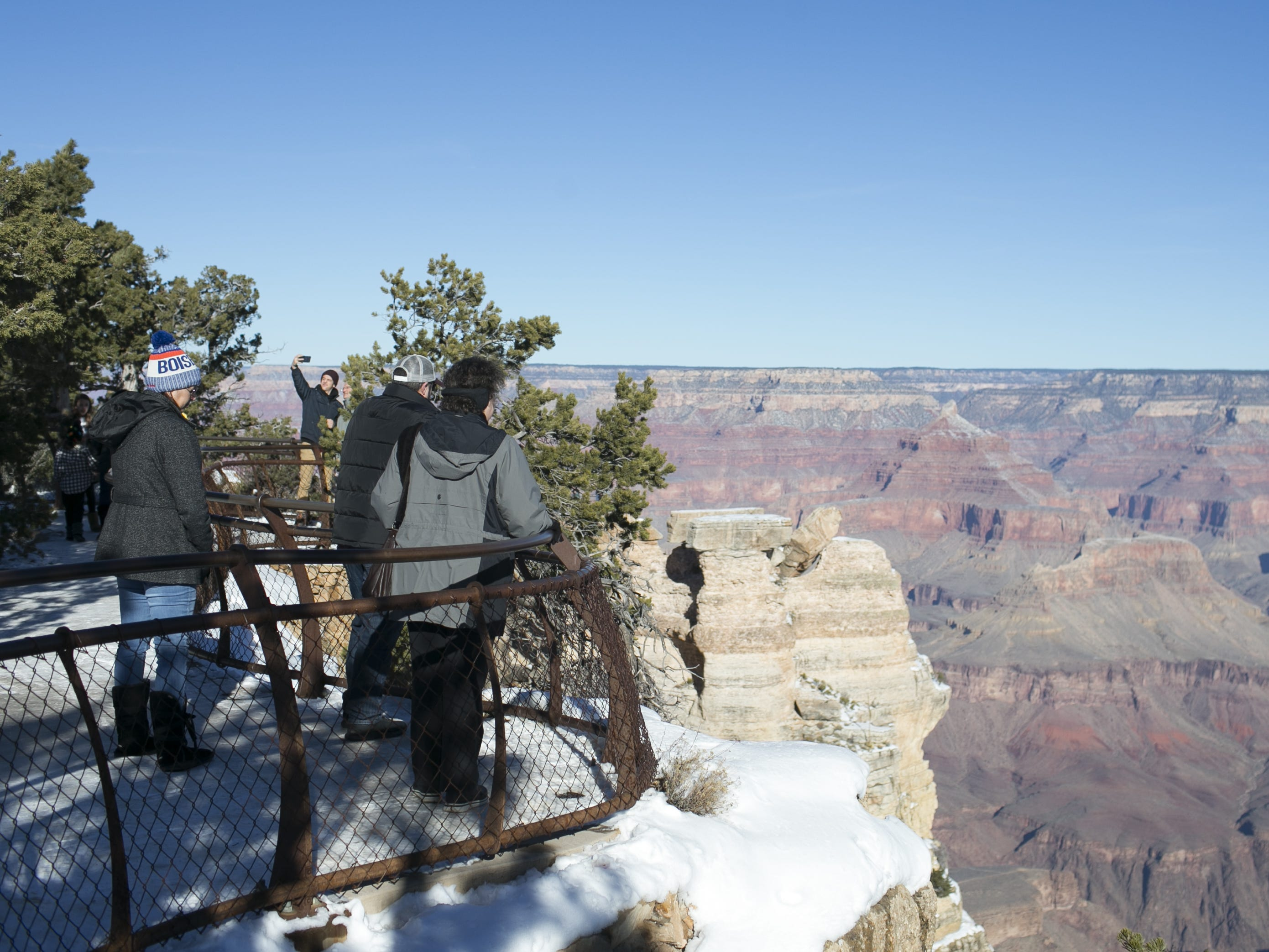 Visitors look out over the edge at Grand Canyon National Park. Fences and railings mark the boundaries of the canyon's edges, but are not too tall to scale.