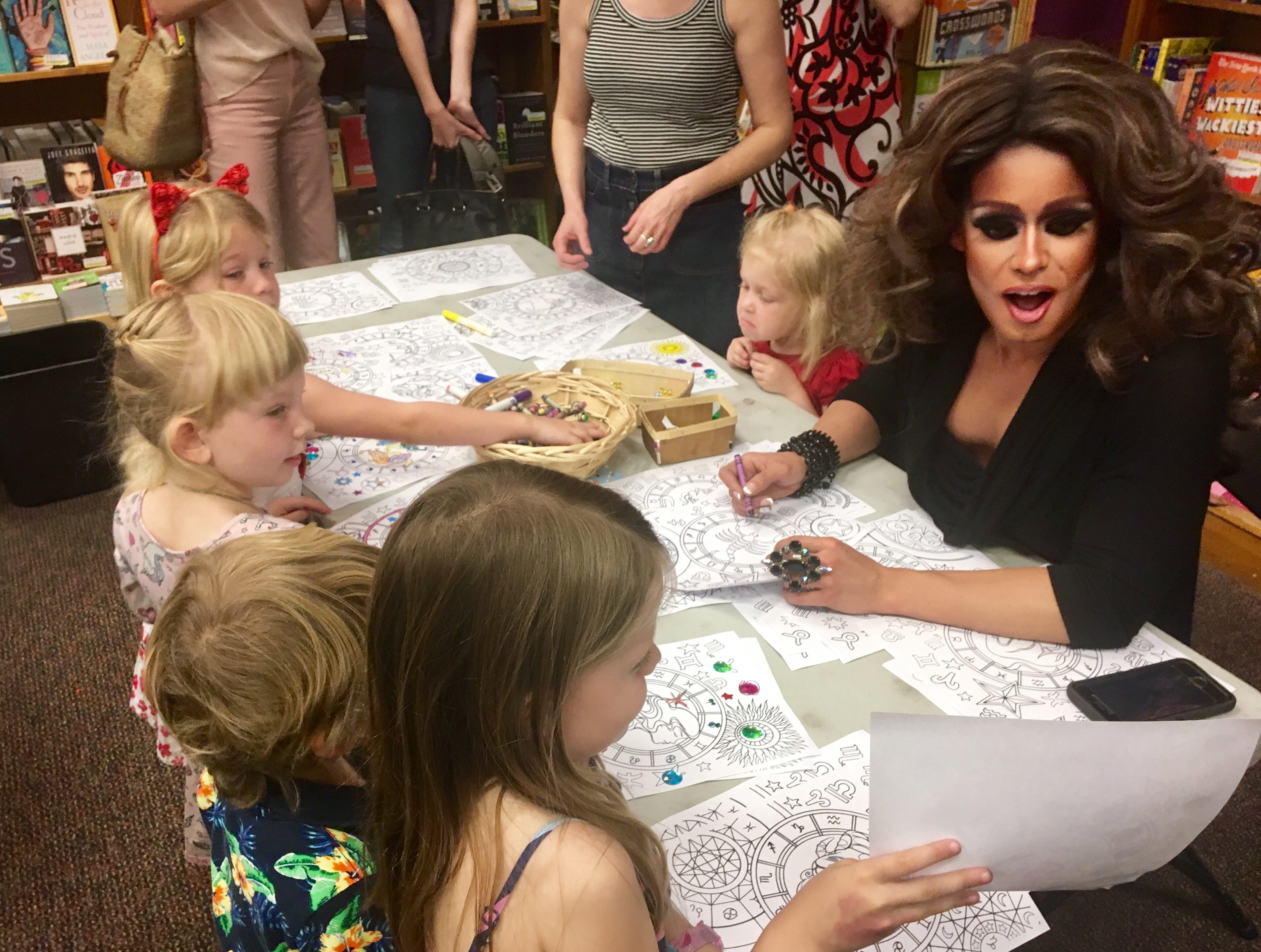 Drag queen Nevaeh McKenzie compliments 5-year-old Gwen Crum on her artwork after Drag Queen Storytime at Changing Hands Bookstore in Tempe.