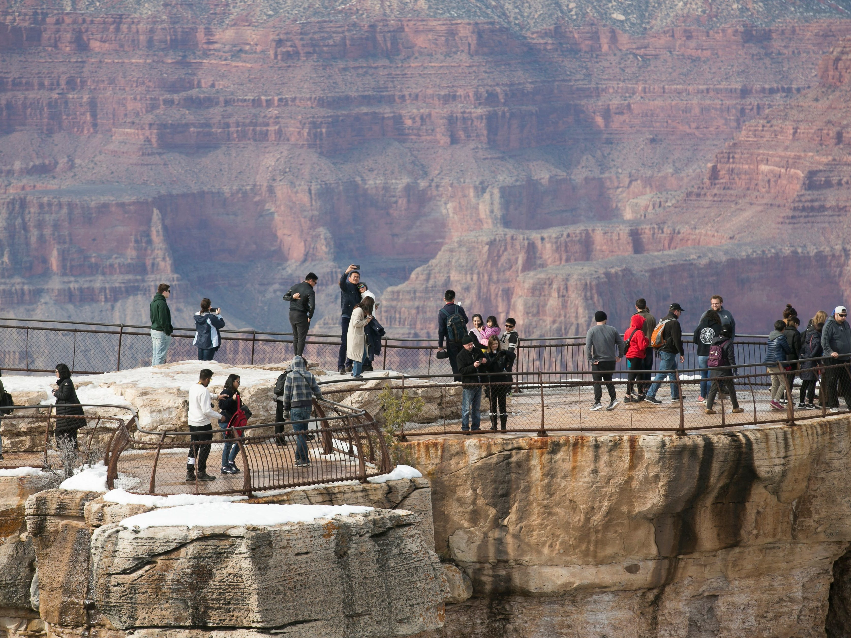 Railings and fences define the edges of the rim at Grand Canyon National Park, but some visitors push the boundaries to explore further.